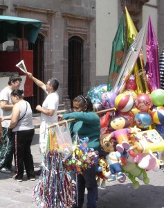 Balloons and toys sell briskly in the Jardin...